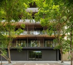 ACA Architects painted the concrete black to contrast with the metal elements, which look like wood but are lighter and stronger.  Real timber features on the modern balconies, which have been given a traditional twist with a half screen of wooden poles.