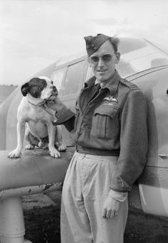 """Wing Commander W G G Duncan-Smith, Wing Commander Flying, No. 244 Wing RAF, with """"Bonzo"""", a bulldog mascot of one of the squadrons of the Wing, standing by his personal communications aircraft, a commandeered Italian Saiman 202, at Tortorella, Italy."""