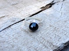 A stunningly faceted or rose cut black onyx 8mm stone has been set in a sterling silver tube setting. The stone is in a bullet shape, ending with a peak giving the ring an edgy, but elegant look. A ha