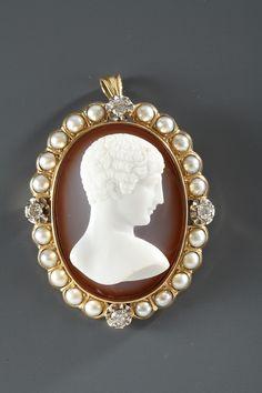 Camée coquillage représentant un buste de jeune homme vu de profil se détachant sur un fond en dégradés de rouge, dans un entourage perlé. La monture or est sertie de...