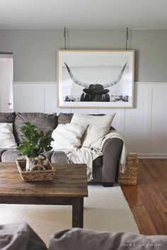 Masculine and rustic living space with dark wood coffee table, bull artwork, gray sofa, and cozy white pillows