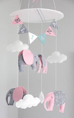 Adorable elephant mobile that adds the perfect touch to the modern nursery! Features 4 elephants, 4 clouds, and pendants with your childs name machine embroidered on (double sided). The top of the mobile also sports a matching chevron embroidered base. This design is a true statement