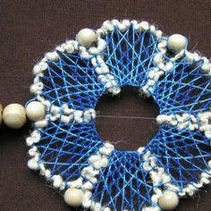 Tři modré kvítky s konturou z bílé pletací příze, navlečené na vlasci a oddělené dřevěnými korálky (ty zároveň slouží jako závaží).