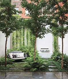 A lush, ground-floor garden in Carnegie Hill, New York City is filled with ginkgo biloba trees, an existing fountain with an Italian marble spout designed by Thomas Woltz, and bluestone pavers. The terrace is filled with woodland greenery: Leucothoe, ostrich ferns, and lady ferns.    This originally appeared in These 7 Lush Landscapes Will Make Your Winter Blues Melt Away.