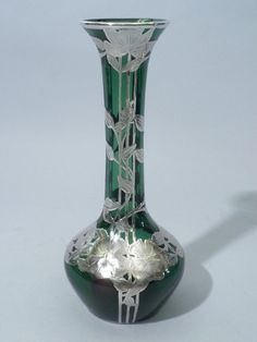 """This beautiful Art Nouveau Circa 1900 silver overlay vase has emerald green glass and is intricately design with large flowers and leaves. Large flowers cover the base of the vase and just below the upper rim. The leaves intertwine around the neck of the vase. The vase measures 10"""" tall and has a long neck measuring about 6"""". It does have Alvin hallmarks and is also marked 999/100 G3485-1"""