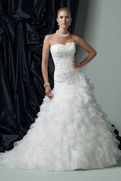 Strapless organza ball gown, beaded re-embroidered lace bodice accented with three-dimensional lace flowers, asymmetrically dropped waistline, multi-tiered full ruffle skirt with chapel length train. Available in Ivory and White.