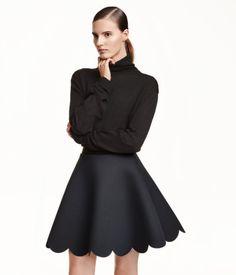 Circle skirt in scuba fabric with an elasticized waistband. Scalloped edge at hem.
