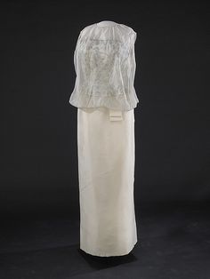Jacqueline Kennedy's Inaugural Gown, Off-white sleeveless gown of silk chiffon over peau d'ange. Its strapless bodice under the chiffon covering is encrusted with brilliants and embroidered with silver thread. Ethel Frankau of Bergdorf Custom Salon designed and made the dress based on sketches and suggestions from Mrs. Kennedy. It was worn with a matching cape (not displayed).
