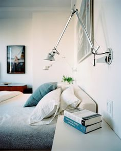 Swing-arm sconces above an upholstered bed