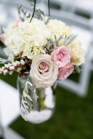 Hang flowers on shepherd's hooks or on chairs along the aisle...can be moved after ceremony to re-use for reception