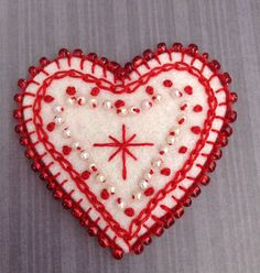 Red and cream felt heart with blanket stitch beading.