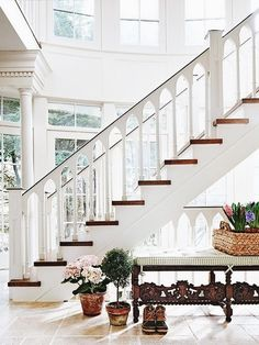 Bright, white, and airy - loving those wood and white stairs and the details in the rungs, so many windows!