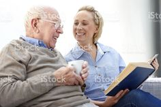 Happy senior man with carer reading a novel together royalty-free stock photo