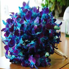 A bright and vivid Bridal Hand Tied Bouquet of Blue-Purple Dendrobium Orchids on a silver colored holder.  Works well with the lavender accented wedding and deep blue wedding accents (see deep blue flower girl dress).