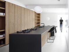 cozinha escondida de madeira e ilha com bancada preta