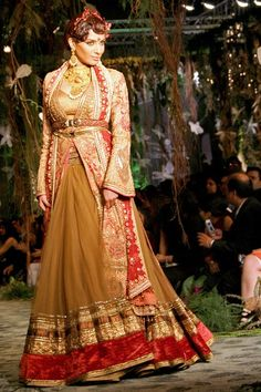The appearance of Diandra Soares heralds a change in palette, with this regal olive ghagra worn underneath a red and gold panel jacket.. By Tarun Tahiliani