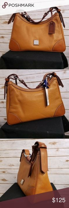 """Dooney & Bourke Harrison Hobo Bag - Caramel NWT The Pebble Grain Collection. Leather. Featuring a relaxed, slouchy crescent-shaped construction, this shoulder bag is the epitome of casual, fashionable style. H 9"""" x W 5"""" x L 13.25"""" One inside zip pocket. Two inside pockets. Cell phone pocket. Inside key hook. Strap drop length 8"""". Lined. Feet. Zipper closure. The leather has gone through extensive tumbling to create the supple texture. Treated for water repellency, the bags are also lined in…"""