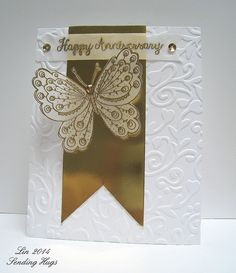 handmade anniversary card by quilterlin ... white and gold ... shiny gold fishtail banner ... embossing folder texture of swirly vine and hearts ... delightful vellum butterfly with intricate pattern gold embossed on its wings ... perfect for a Golden Anniversary  ... or any other ...