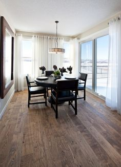 I really like the raw wood floors with the floor to ceiling windows with flowy curtains. The mixture of rustic and modern is great. I would put a different table but this is definitely unique and a check in my like column
