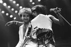 Rock group Queen in concert at Wembley Arena. Lead singer Freddie Mercury performing on stage on his birthday, in drag with his arm around bass guitarist Roger Deacon. Elizabeth Taylor, Roger Taylor, Brian May, John Deacon, Aretha Franklin, Best Rock Bands, Cool Bands, Jimi Hendrix, Recital