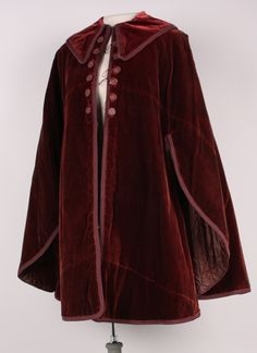 Date Made: c. 1845-55 Description: Mantle; deep rust or brown velvet with silk cord trim, 12 decorative buttons. Pointed collar with hook and loop closure. Openings on side for arms. Center back panel is rounded on the sides. Center front opening with 6 thread covered buttons and loops on each side of opening. Lined in a quilted brown silk.