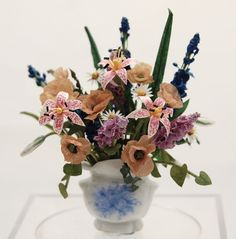 Marjorie Meyer, IGMA artisan - floral arrangement featuring poppies, oriental lily, hollyhocks, daisy, and delphinium flowers set in a two handled porcelain urn vase