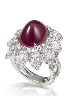 A ruby and diamond ring  Designed as a flowerhead, centring on an oval sugarloaf cabochon ruby, weighing 12.18 carats, within a brilliant-cut and pear-shaped diamond surround, to a similarly-cut diamond gallery and half-hoop, mounted in platinum, the diamonds estimated to weigh approximately 4.12 carats in total