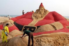"""Sand sculpture artist Sudarsan Pattnaik, along with some of his students, have created a huge sand installation that features 500 Santa Clauses sculpted into the sand at a beach in India. At the top of the sculpture reads the message """"Go Green, Save the Earth"""". Be sure to head over to Pattnaik's website to see more of his work."""