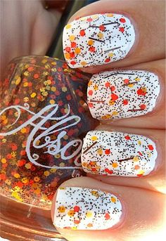 A fun looking depiction of falling leaves atop a white base polish with added multi colored glitter on top.