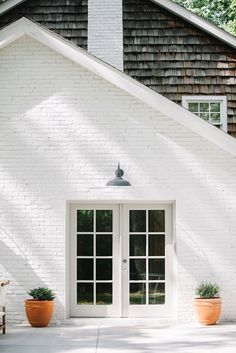 Fresh and modern farmhouse exterior with sunwashed shingles and white painted bricks.