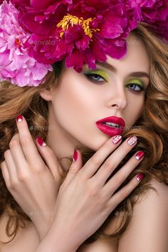 Close-up beauty portrait of young pretty girl with flower wreath in her hair wearing bright pink lipstick and touching her lips. Bright modern summer makeup. Beauty, spa, manicure  and skincare con...
