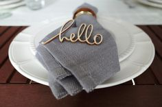 Hello decor on the plates. Gray napkins, white plates with carving.