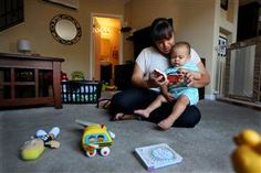 Image: Marisa Mauer,34, reads a book with her 13-month-old son Nathaniel at their home in San Diego, Calif.
