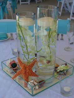 Centro de mesa.. Cilindros con agua y orquideas sumergidas, conchas y arena.