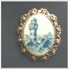 Vintage lighthouse brooch pin on porcelain Beautiful vinyage brooch featuring a lighthouse on porcelain.  Can also be worn as a necklace pendant. 2 inches high and 1.5 inches wide. Very good condition. Jewelry Brooches