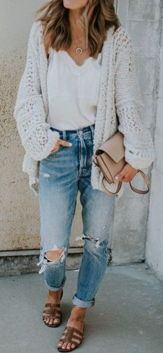 must have levis jeans wearing with a white blouse coveres with a knit cardigan