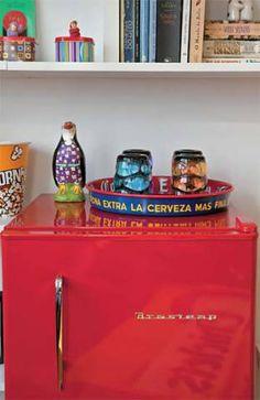 Charmosa, a minigeladeira fica em plena sala. Dessa forma, poupa espaço na cozinha, que tem apenas 2,20 m2. Mas, para que fizesse parte da decoração do ambiente mais importante do apê, Denise elegeu um modelo retrô e de cor forte, sobre o qual arruma copinhos em uma bandeja – assim, ainda facilita o serviço no dia a dia. O modelo Retrô (48x51x80cm), de 76 litros, é da Brastemp. Fast Shop, R$ 897,83 (ou 10 x R$ 99,90). Para completar, o pinguim arremata o visual descolado.