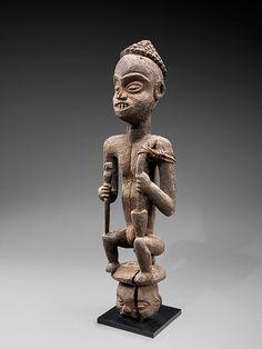 Statue d'ancêtre Peuple Bangwa  Cameroun  Bois, vannerie  Hauteur : 64 cm.   Cette statue commémorative représente un roi assis, comme le montrent ses attributs de cérémonie, principalement le couvre chef, l'épée et la pipe, qui sont typiques des regalia Fon. Pendant les cérémonies, les statues reçoivent d'importantes libations sacrées qui contribuent à la formation de l'épaisse patine noire croûteuse.