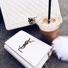 Badass bags and wallets together with coffee, phone white fluffy creature...