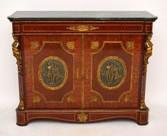 Very impressive marble top cabinet with amazing gilt mounts all over. It's antique French style & I would say it dates to around the 1930-50's period. The gilt mounts are stunning & the quality of the castings is very good. The panels in the centre of the doors look like solid bronze & they are spectacular. The wood is mainly Kingwood, Rosewood & Mahogany, with some inlaid woods in places. The marble top is in perfect condition & a lovely colour.