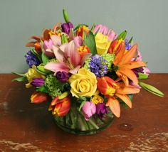 Bright and colorful arrangement of hyacinth, roses, tulips and lilies