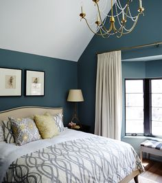Dark paint on the walls of this bedroom evoke a cosy, luxurious mood. Hits of warm metal on the glam chandelier, table lamp and curtain rod enhance the opulence. | Wall colour, Templeton Gray (HC-161), Benjamin Moore. | #paint #decor