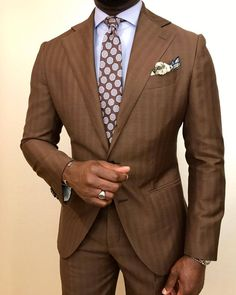 Wide lapel brown striped suit with brown and light blue large geometric design necktie