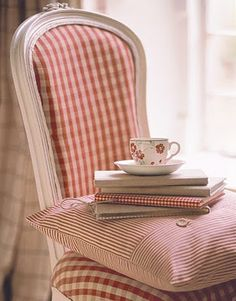 White painted chair, red checks, with red books and cup