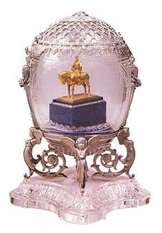 "1910 - Aleksandr III Equestrian Egg. The egg is carved from engraved rock-quartz crystal. Half the egg is covered with platinum trelliswork and a tasseled fringe,the consoles set with rose-cut diamonds. A large diamond engraved with the year ""1910"" surmounts the egg.   The lower part of the egg is a platform for a gold model of a statue of Czar Aleksandr III on horseback on a nephrite base with two rose-cut diamond bands. Platinum cherubs support the base of the crystal."