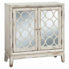 """Distressed cabinet featuring 2 mirrored doors with geometric wood overlay and an adjustable shelf.   Product: CabinetConstruction Material: Wood and mirrored glassColor: Off whiteFeatures:  Distressed finishTwo mirrored doorsHandsome geometric wood grillesOne adjustable shelf Dimensions: 34"""" H x 32"""" W x 15"""" D"""