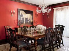 Walls finished in a vibrant marmorino plaster add punch to the dining room; the crystal chandelier and faux coral branches are from JF Chen, and the sconces are by Formations.