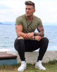 Outfit masculino com camiseta verde militar, calça preta ripped e tênis branco cano médio. Veja mais dicas de moda com a cor verde militar no blog Marco da Moda - Foto: Shane Crommer