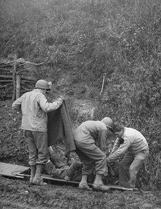 Battle Of The Bulge - Helping wounded and dead soldiers during Battle of the Bulge fighting near Malmedy, where Germans have broken through the lines. 1945.