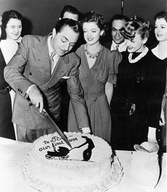 """Watched by Myrna Loy, Virginia Grey and other cast members, William Powell cuts his birthday cake on the set of """"Another Thin Man"""" - ONE OF MY FAV SERIES"""